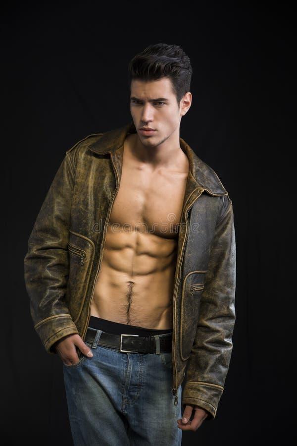 在赤裸躯干的英俊的年轻人佩带的皮夹克 免版税库存图片