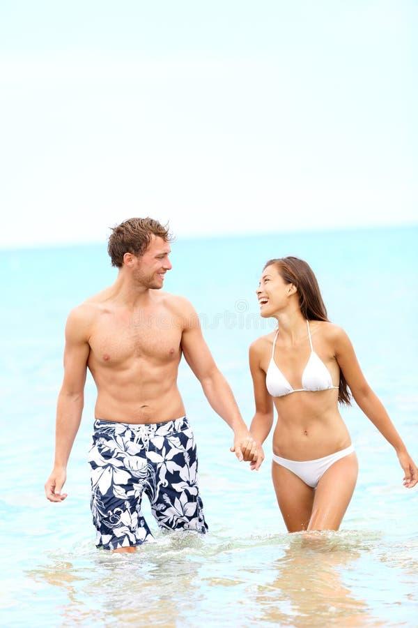 在走在水中的海滩的夫妇 图库摄影
