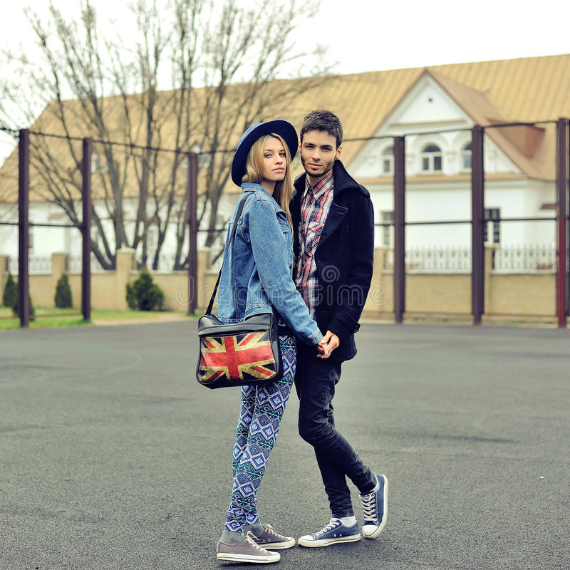 在走在城市的爱的年轻夫妇停放握手 库存照片