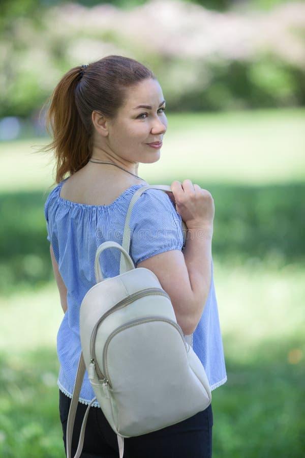 在走在夏天公园,米黄背包的pleasured妇女的背面图垂悬在肩膀 库存图片