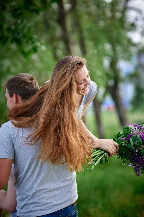 在走在夏天的爱的年轻夫妇停放 免版税库存图片