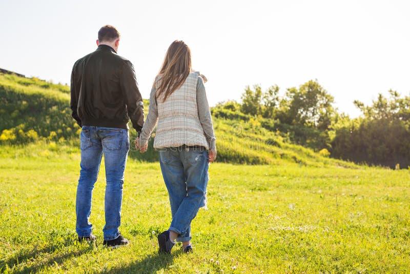 在走在秋天的爱的年轻夫妇停放握看在日落的手 免版税库存图片