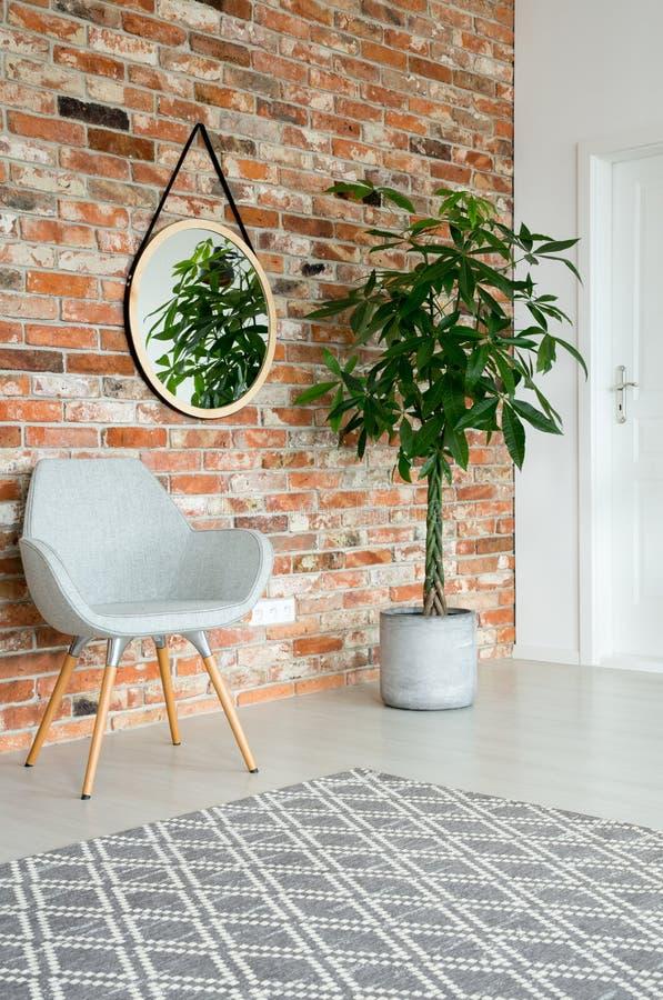 在走廊墙壁上的镜子有高植物的罐、灰色时髦的椅子和砖墙的 免版税库存照片