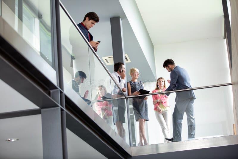 在走廊悠闲谈话的商人 免版税库存照片