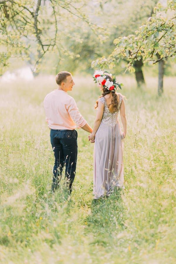 在走的爱的夫妇户外拿着手、可爱的年轻人和妇女佩带的花圈在日期,看彼此,后面 免版税图库摄影