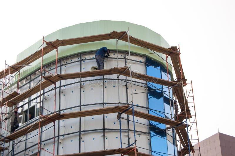在走道的建筑工人身分依据为给上釉在大厦门面做准备建设中 免版税图库摄影
