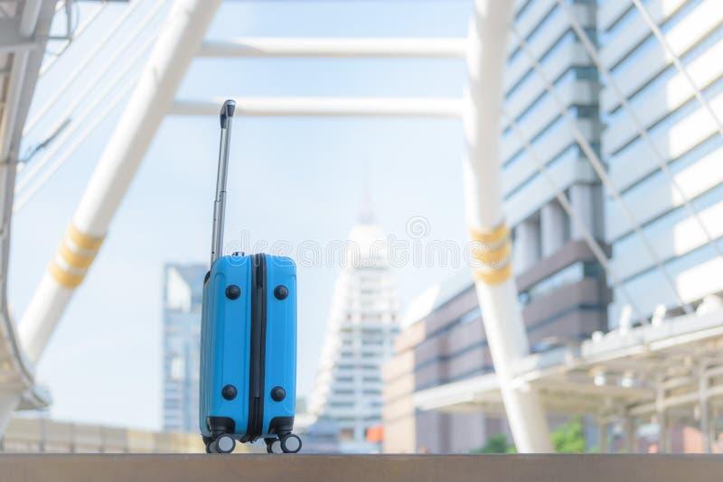 在走道的蓝色旅行包有被弄脏的城市背景 免版税库存照片