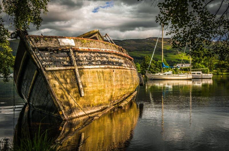 在起波纹的奈斯湖湖的老被放弃的小船在苏格兰 图库摄影