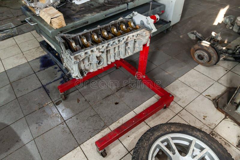 在起重机的替换引擎登上用于设施在汽车在故障和修理以后在汽车修理车间作为a 库存照片