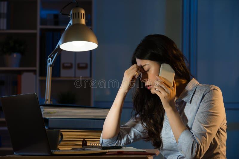 在超时运转的智能手机的亚洲女商人头疼 库存照片