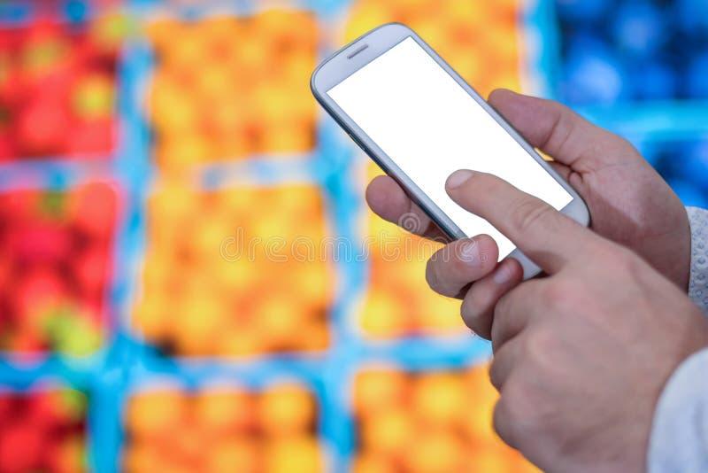 在超级市场供以人员检查在她的智能手机的购物单 图库摄影