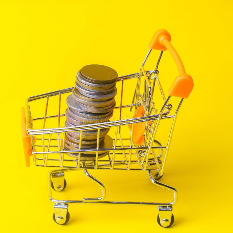 在超级市场台车的硬币 财务和金钱的概念 在一个新的项目的一种投资 财富和贫穷 在的购物 免版税库存图片