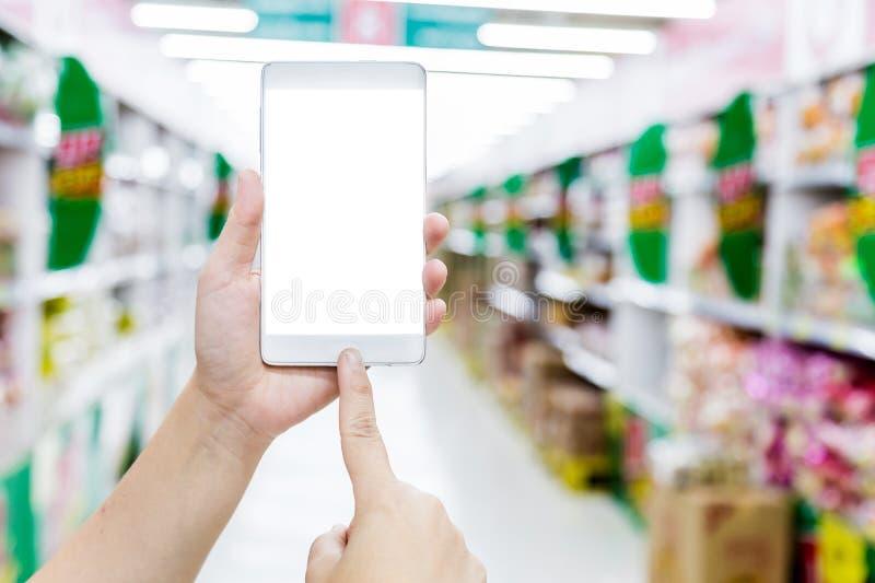 在超级市场和检查购物的女性手举行智能手机 免版税图库摄影