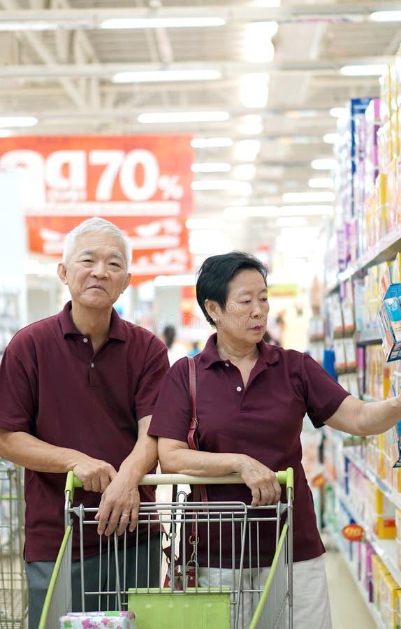 在超级市场的亚洲资深夫妇购物 免版税库存照片