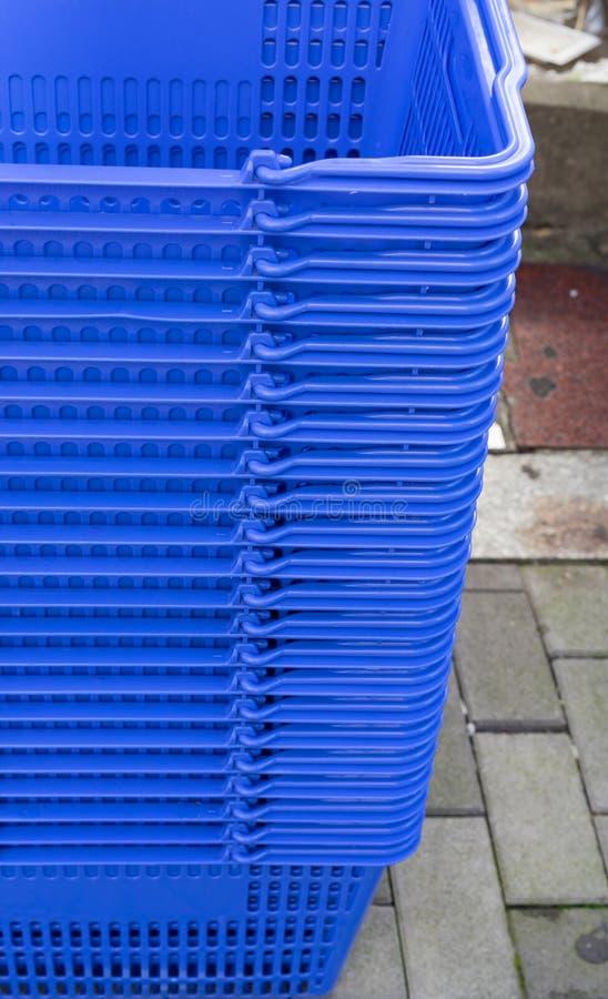 在超级市场的堆蓝色塑料篮子 免版税库存图片