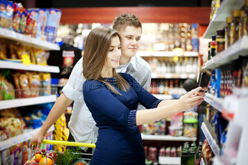 在超级市场的新夫妇购物 库存照片