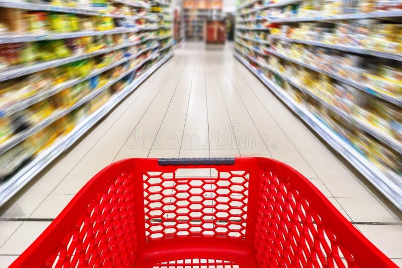 在超级市场走道的红色空的手推车 免版税库存图片
