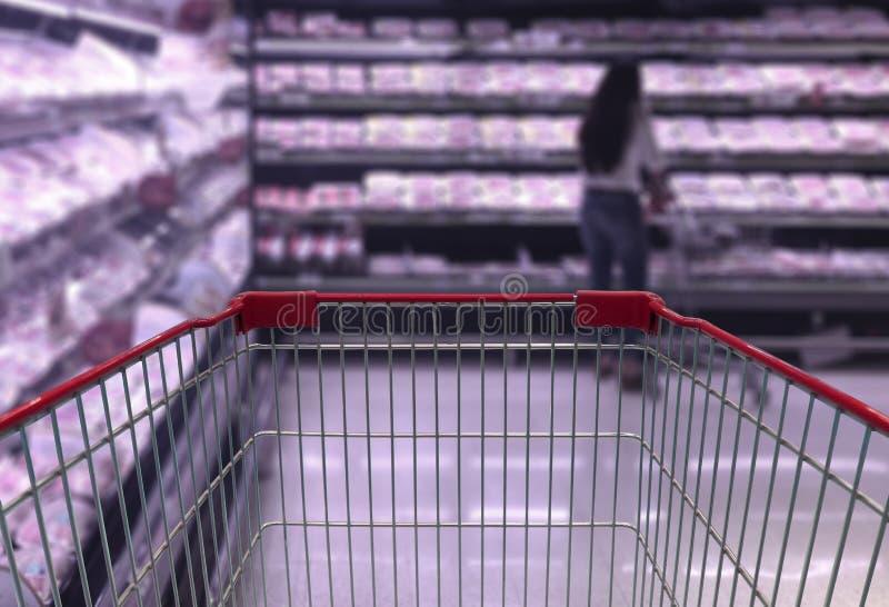 在超级市场走道的购物车视图有产品的搁置  免版税库存图片