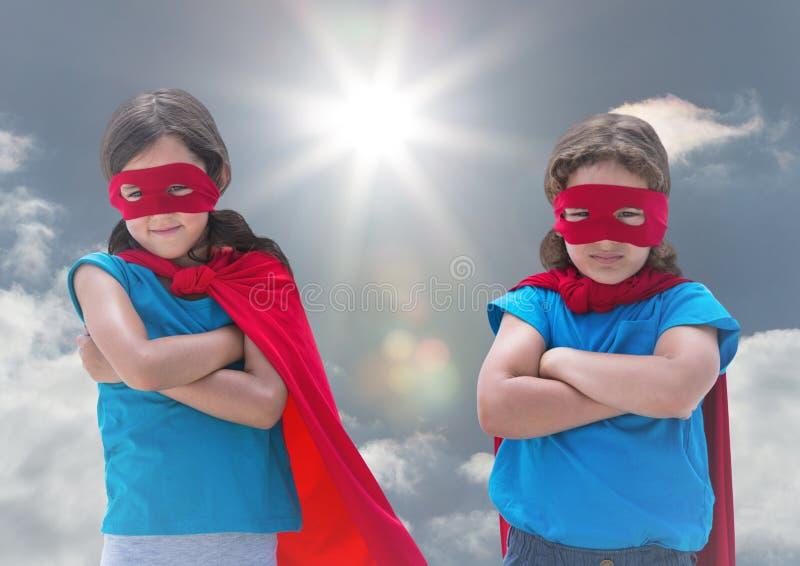 在超级英雄的孩子在背景中打扮与胳膊的身分横渡反对天空 库存例证