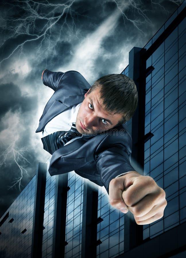 在超级英雄的生意人街市飞行 免版税图库摄影