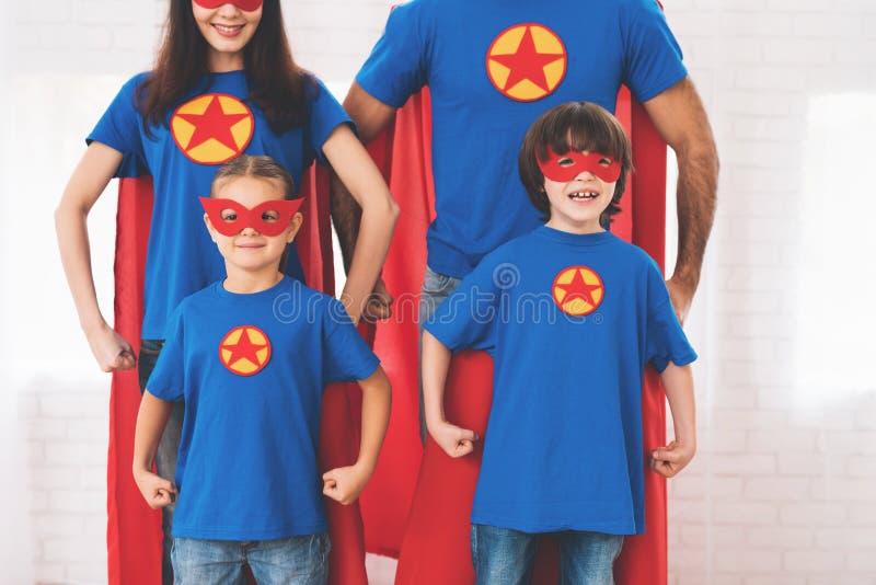在他们的面孔是面具,并且他们在雨衣 他们在一间明亮的屋子摆在 孩子图片