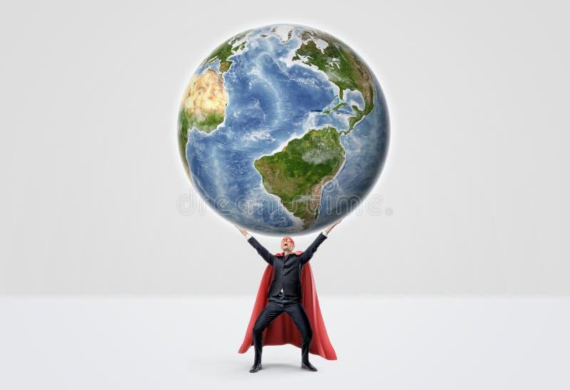 在超级英雄红色海角的一个微笑的商人用手在拿着在白色背景的成功行动上升了地球 免版税库存照片