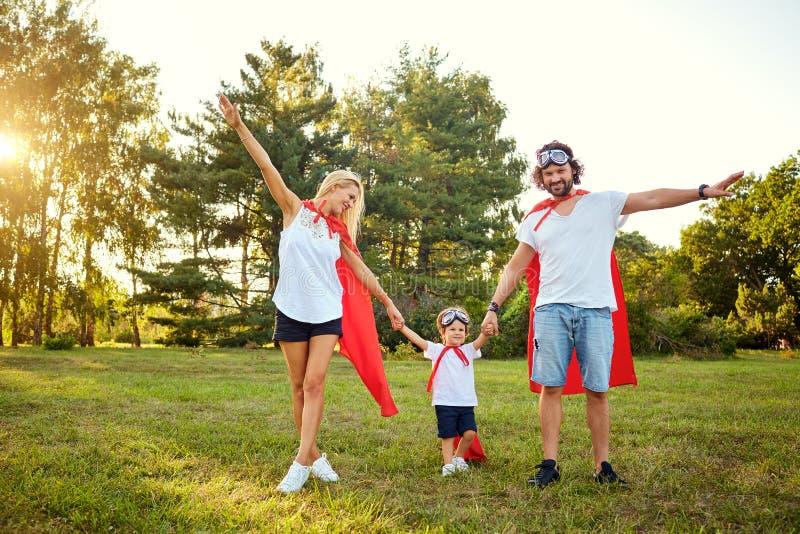 在超级英雄衣服的愉快的家庭在公园 免版税库存图片