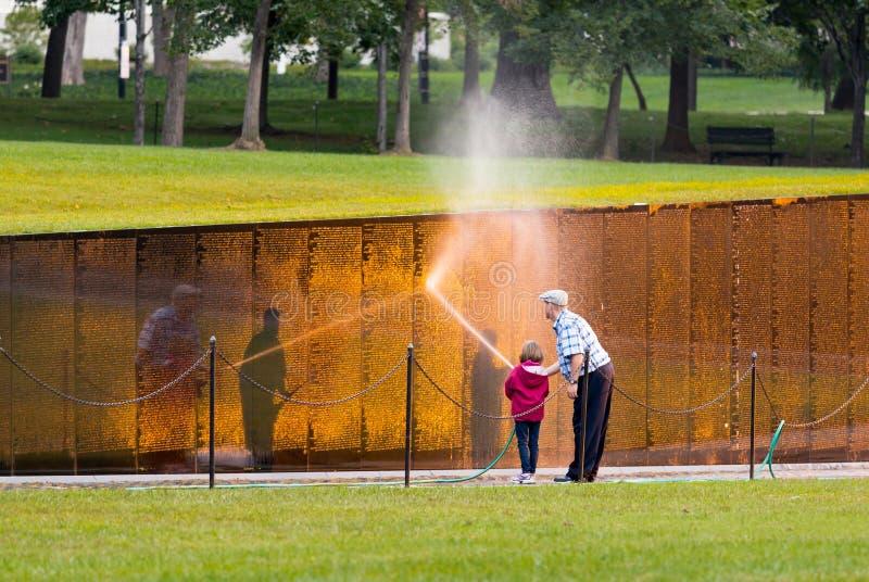 在越南纪念品的人和女孩洗涤的墙壁 库存照片