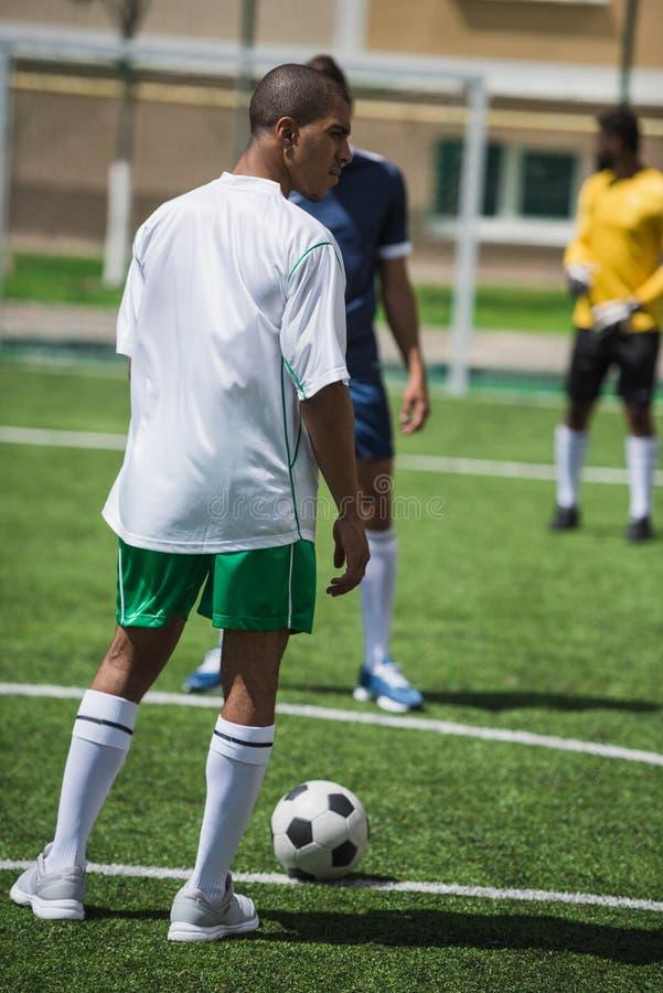 在足球比赛期间的足球运动员在沥青 库存图片