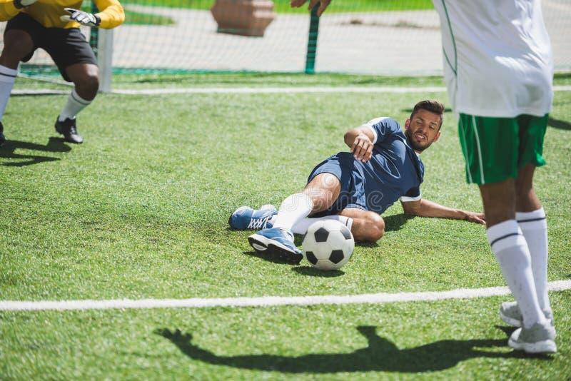 在足球比赛期间的足球运动员在沥青 免版税库存图片