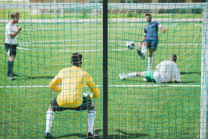 在足球比赛期间的足球运动员在沥青 免版税库存照片