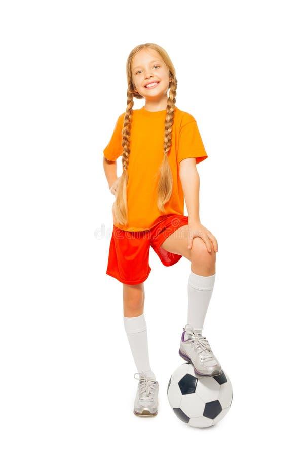 在足球的逗人喜爱的白肤金发的女孩立场在演播室 图库摄影