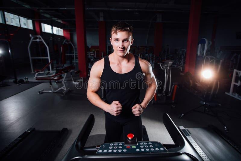在跑在有水瓶的踏车的健身房的年轻强的大人健身模型 库存照片