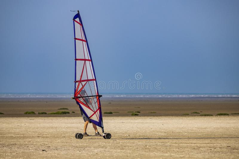 在跑在沙子的海滩的Windskate 图库摄影