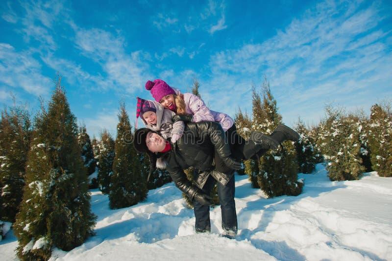 在跑明亮的衣裳冬天的乐趣的年轻美丽的家庭跳跃和,雪,生活方式,寒假 免版税图库摄影