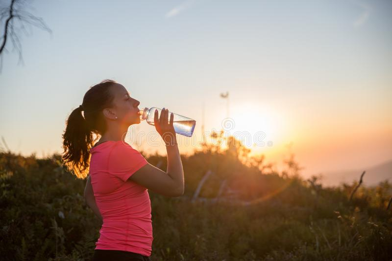 在跑的妇女饮用水在山期间在夏天 库存照片