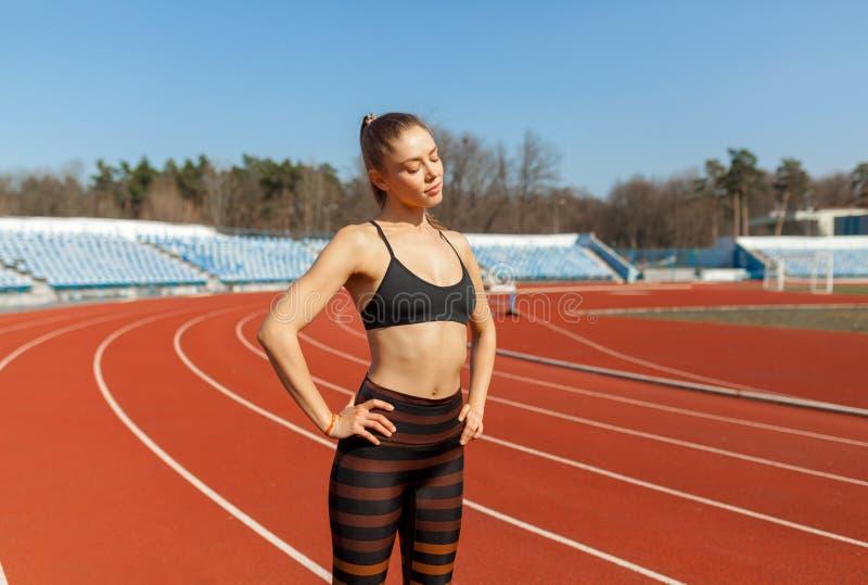在跑的年轻健身妇女赛跑者准备在轨道前 库存图片