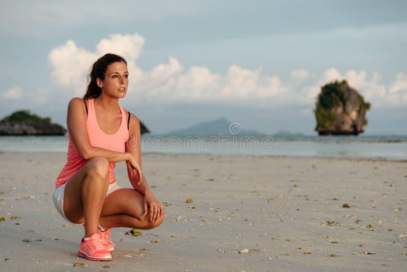 在跑的有动机的运动的妇女在海滩前 图库摄影