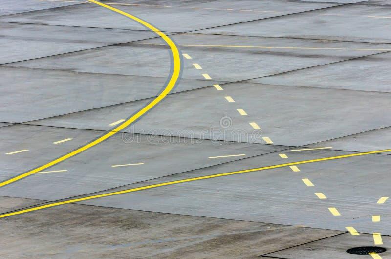 在跑道柏油碎石地面的着陆指示灯定向标志标号在一个商业机场 免版税图库摄影
