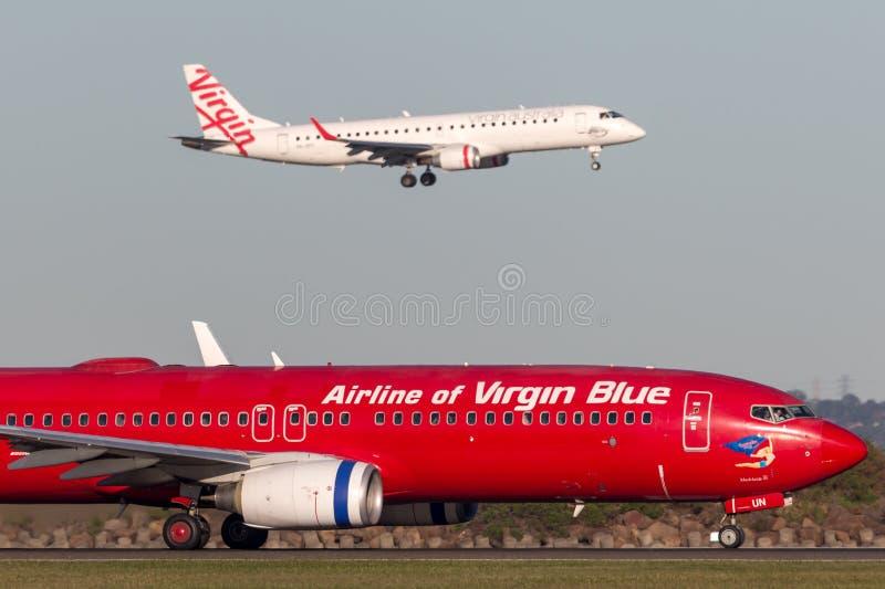 在跑道的和平的蓝色航空公司维尔京澳大利亚航空公司波音737悉尼机场的 免版税库存照片