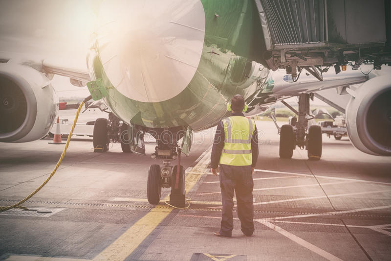 在跑道的技工支持的飞机 免版税库存图片