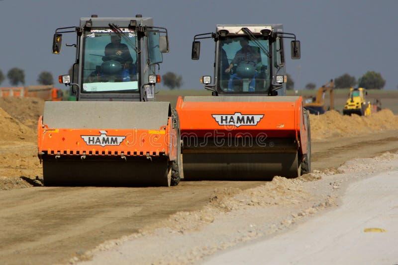 在跑道建造场所的重型建筑设备变紧密的土壤 免版税库存图片