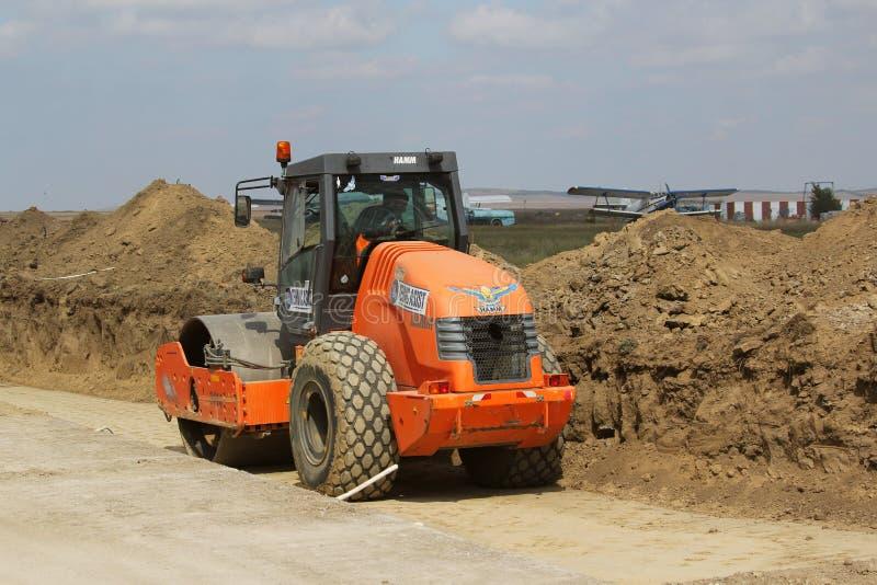 在跑道建造场所的重型建筑设备变紧密的土壤 库存照片
