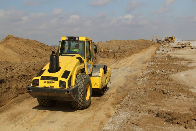 在跑道建造场所的重型建筑设备变紧密的土壤 库存图片
