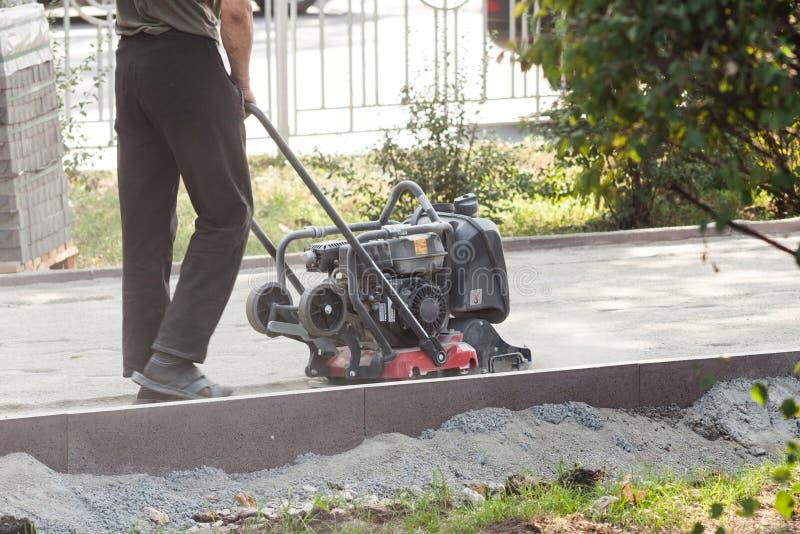 在路修理的工作者用途振动的板材压紧机变紧密的地面 在路面前的准备被铺 库存照片