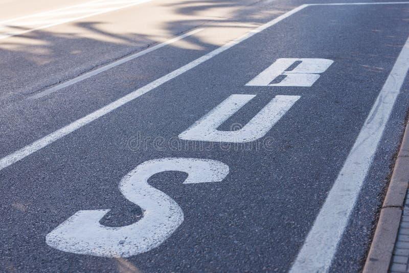 在路公共汽车,在沥青、信息和征兆信号绘的标志的细节的标志 库存图片