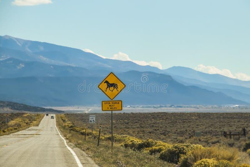 在路和汽车的热淡光在有山的高沙漠在距离和与说开放范围的马的一个标志 库存照片
