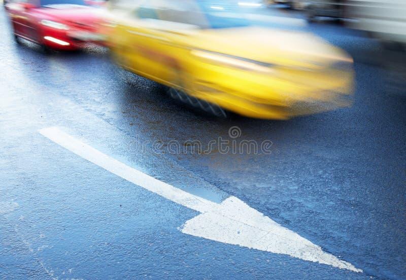 在路和移动的汽车的箭头 免版税库存照片