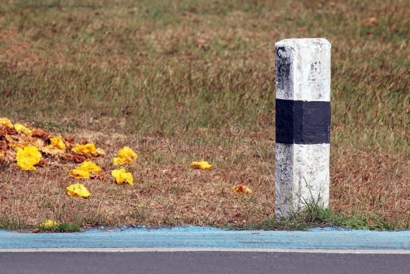 在路旁的具体公里标志杆有自然草背景、混凝土桩公里在路和黄色 免版税库存图片