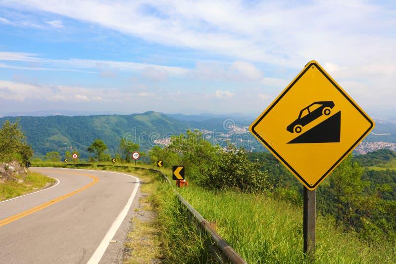 在路旁边的警告的倾斜标志,对注意的黄色标志对下坡路 免版税库存照片